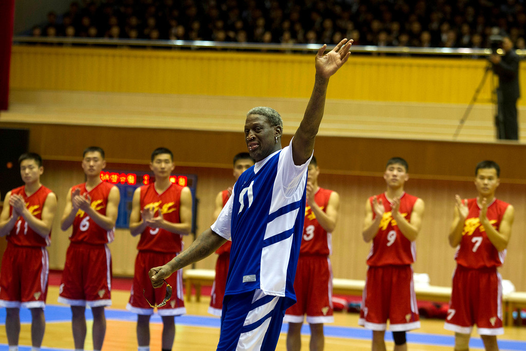 . Dennis Rodman waves to North Korean leader Kim Jong Un, seated above in the stands, after singing Happy Birthday to Kim before an exhibition basketball game with U.S. and North Korean players at an indoor stadium in Pyongyang, North Korea on Wednesday, Jan. 8, 2014. (AP Photo/Kim Kwang Hyon)