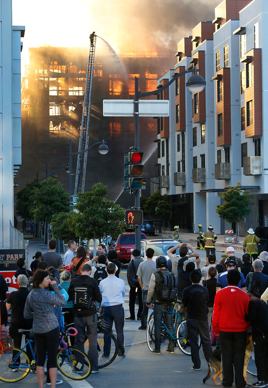 . Spectators on the intersection of China Basin and Third Street watch firefighters battle a multi-story blaze in a residential building under construction in the Mission Bay neighborhood of San Francisco, Calif., Tuesday evening, March 11, 2014. (Karl Mondon/Bay Area News Group)