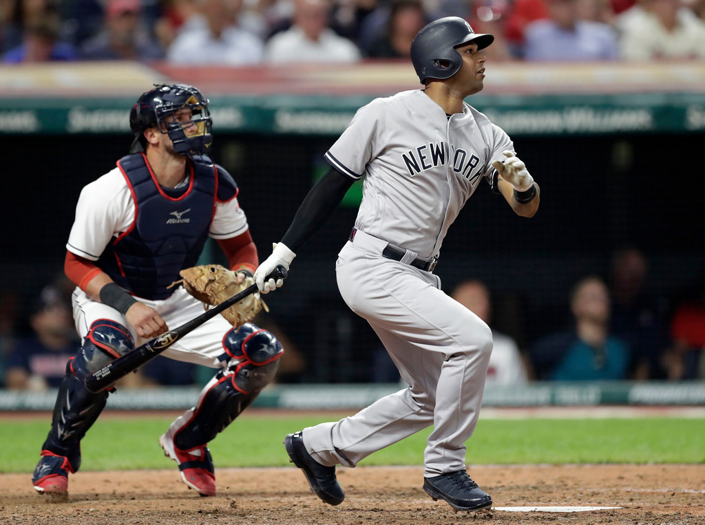 . New York Yankees\' Aaron Hicks watches his RBI double off Cleveland Indians starting pitcher Corey Kluber during the eighth inning of a baseball game, Thursday, July 12, 2018, in Cleveland. Indians catcher Yan Gomes watches. (AP Photo/Tony Dejak)
