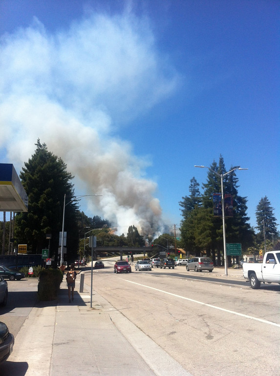 . Blue sky fills with smoke as a wildland fire spreads up a hill on the side of Highway 17. (Colin/Contributed)