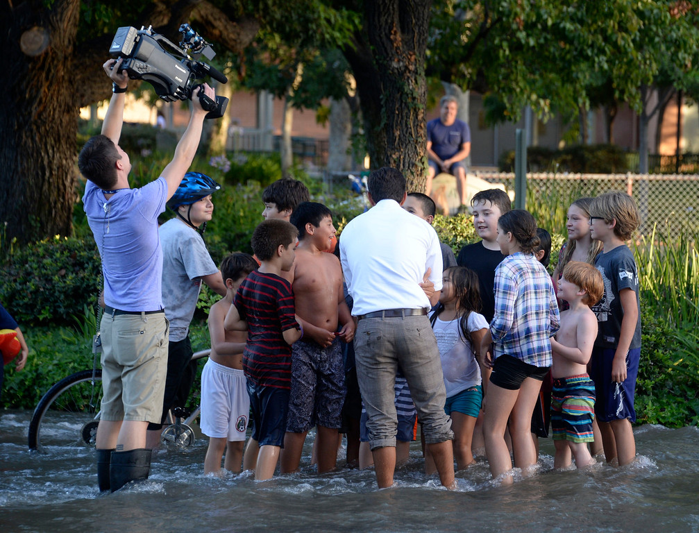 . June 17,2014. Burbank. CA. TV news crews interview kids as they have fun in the water after a 30 inch water main broke at the Burbank Fire training center Tuesday. The water created a river in the streets that were near by the brake but did not flood any homes near by. Burbank water and power crews are on scene working to shut off the water.  Photo by Gene Blevins/LA DailyNews