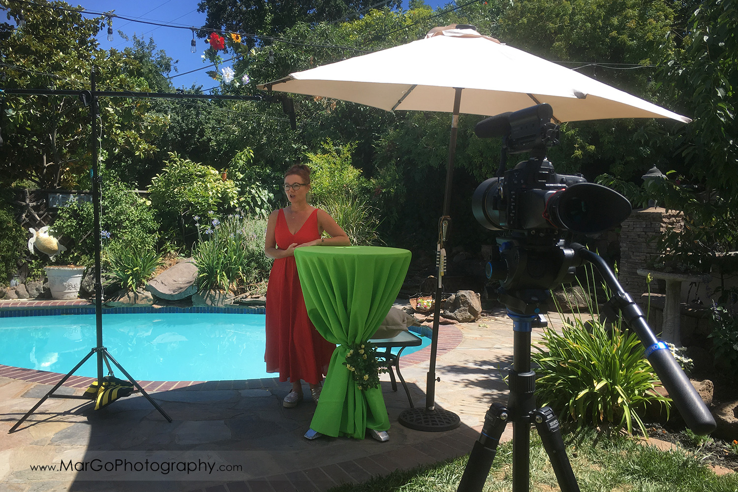 behind the scenes of outdoor filming woman speaker in a red dress