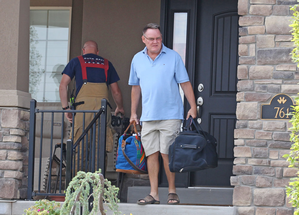 . Home owner Lo Nestman evacuates his home following a landslide in a hillside community of North Salt Lake, Utah, Tuesday, Aug. 5, 2014. North Salt Lake officials say more than 20 homes have been evacuated following an early morning landslide that destroyed one hillside home. (AP Photo/Rick Bowmer)