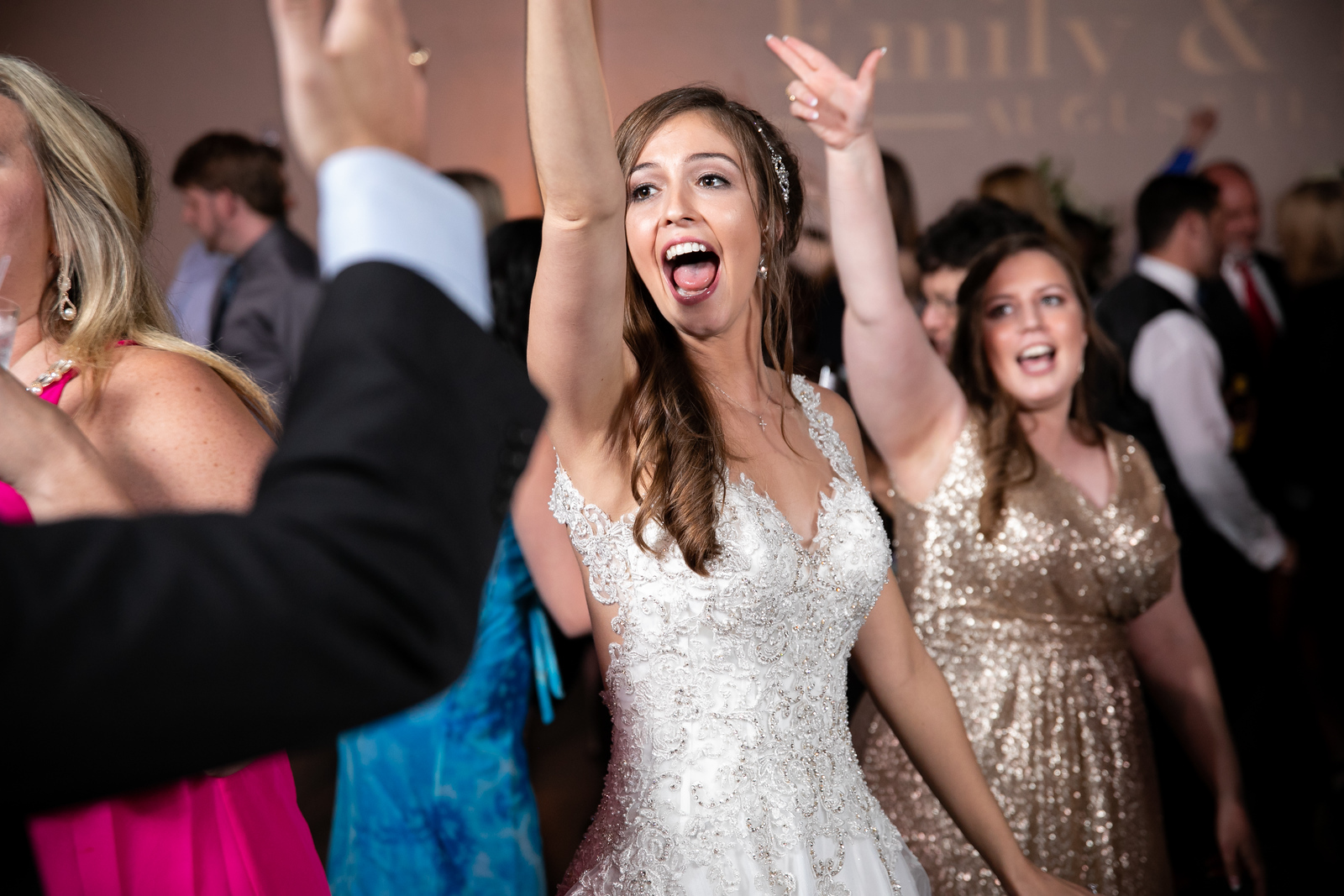 a bride smiling and dancing at her wedding surrounded by friends and family on the dancefloor