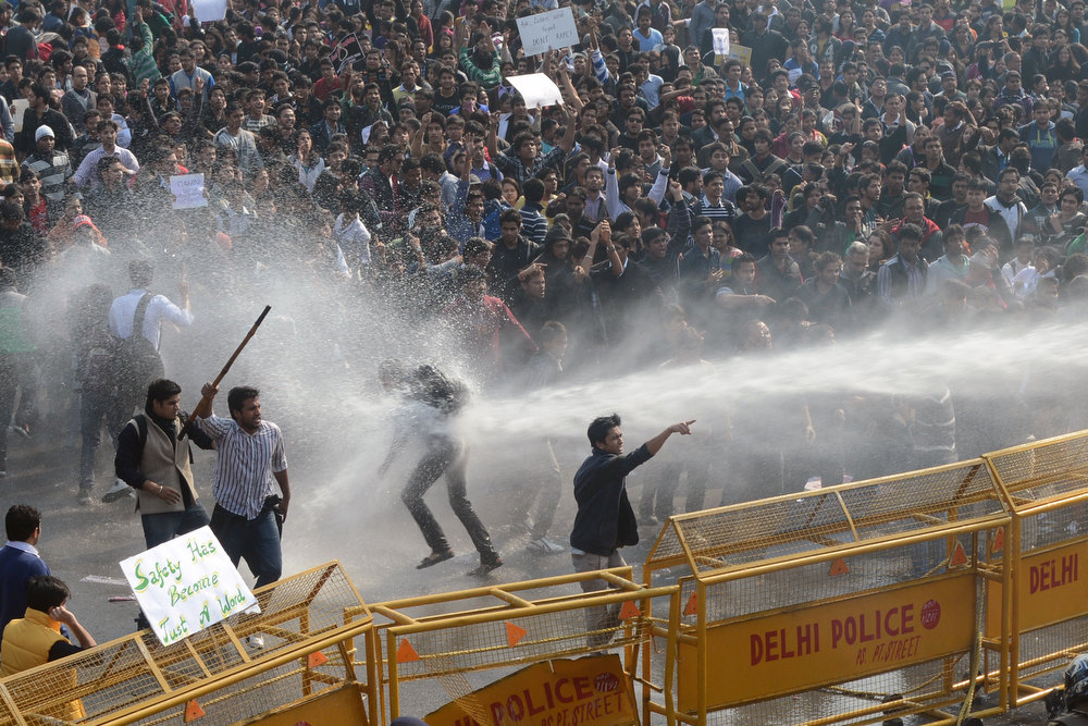 Description of . Demonstrators react as police unleash water cannon during a protest calling for  better safety for women following the rape of a student last week, in front of the Government Secretariat and Presidential Palace in New Delhi on December 22, 2012. Indian police on December 22 baton-charged, tear-gassed and fired water cannon at demonstrators who were demanding better safety for women following the brutal gang-rape of a student last weekend. Thousands of protesters, who rallied at the India Gate monument in the heart of the Indian capital and surged toward the president's palace, were calling for stepped-up security for women across the country. RAVEEN DRAN/AFP/Getty Images