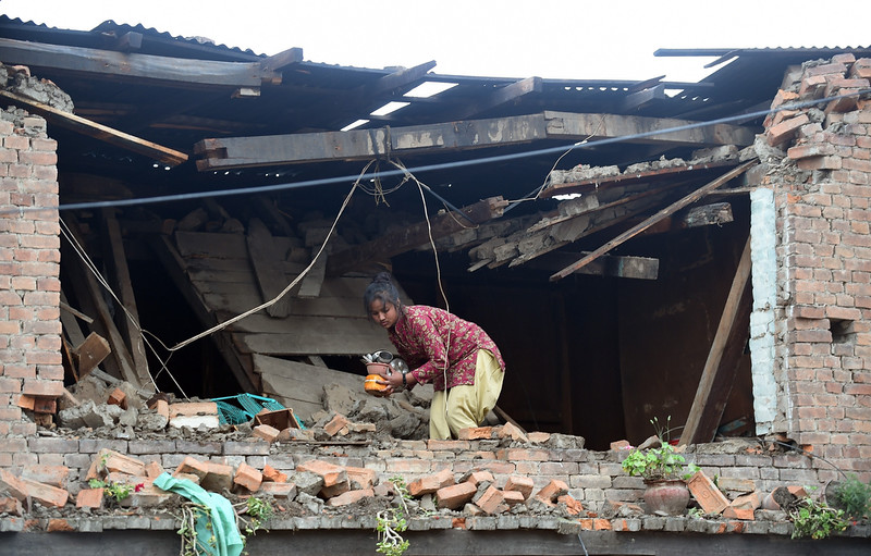 . A Nepalese girl takes out belongings from her damaged house in Bhaktapur on the outskirts of Kathmandu on April 26, 2015. International aid groups and governments intensified efforts to get rescuers and supplies into earthquake-hit Nepal on April 26, but severed communications and landslides in the Himalayan nation posed formidable challenges to the relief effort.  PRAKASH SINGH/AFP/Getty Images