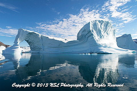 Iceberg Graveyard in Rodefjord, Scoresby Sund, Greenland - Zodiac peeking out under the arch, photo by NSL Photography