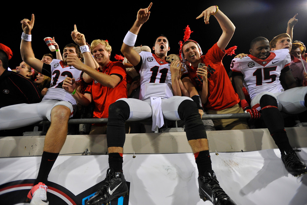 . Georgia\'s Collin Barber (32),  Aaron Murray (11) and  J.J. Green (15) celebrate in the stands with Georgia fans after their 23-20 win over Florida in an NCAA college football game in Jacksonville, Fla., Saturday, Nov. 2, 2013.  (AP Photo/Athens Banner-Herald, AJ Reynolds)