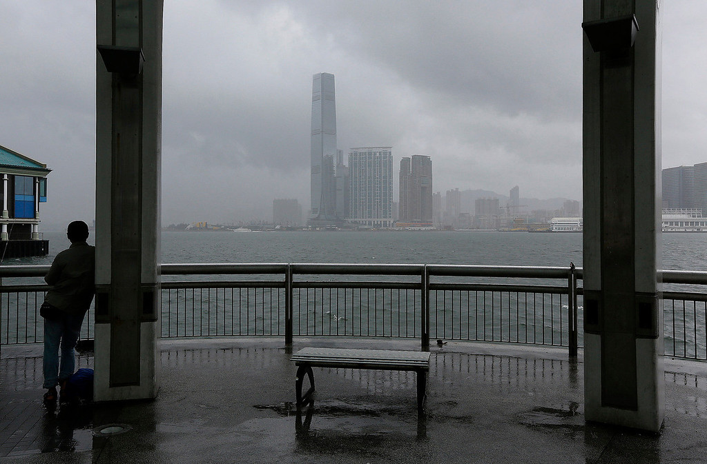 . A man leans against a pillar at Hong Kong\'s Victoria Habour in Hong Kong, Tuesday, Aug. 13, 2013. The Observatory said Typhoon Utor intensified slightly as it moves towards the western coast of Guangdong. Typhoon Utor battered the northern Philippines on Monday, toppling power lines and dumping heavy rain across cities and food-growing plains. (AP Photo/Vincent Yu)