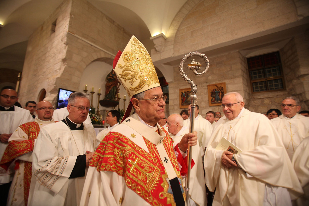 . Foud Twal (C), archbishop of the Roman Catholic Church and serving as Latin Patriarch of Jerusalem, leads a Christmas Eve Midnight Mass at the Church of the Nativity, in Bethlehem, West Bank, 25 December 2013. Thousands of pilgrims made their way to the Church of the Nativity this week to worship at the sacred site believed to be the birthplace of Jesus. Palestinian president Mahmoud Abbas attended the mass.  EPA/MUSA AL-SHAER/POOL