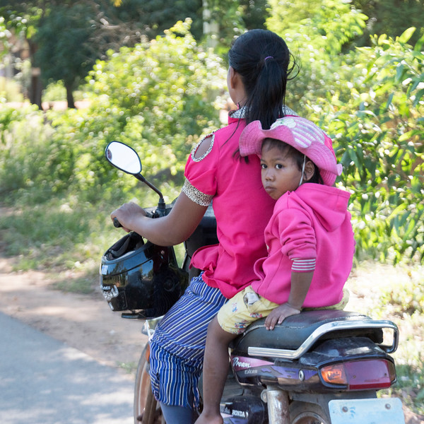 Woman transporting her child on motorbike, Siem Reap, Cambodia