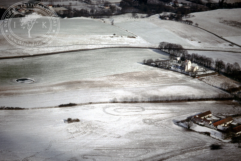 Farmland west of Ravlunda church - with plantations, buildings and prehistoric remains (20 February, 1988). | LH.0201