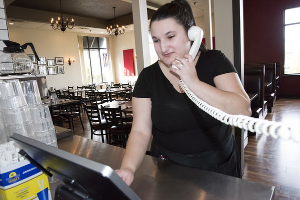03/27/20 Wesley Bunnell | Staff Jenna Martino enters a to go phone order inside of an empty Bell City Diner on Monday afternoon. Health officials shut down all state restaurants at 8p.m. to dining inside while still allowing them to offer deliver and offer to go service.