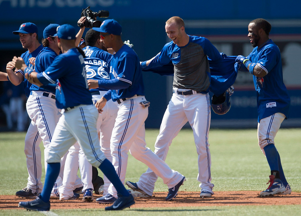 . Toronto Blue Jays\' Nolan Reimold, second from right, is mobbed by teammates after hitting the game-winning RBI double in the tenth inning of a baseball game, Saturday, Aug. 9, 2014 in Toronto. The Blue Jays defeated the Tigers 3-2. (AP Photo/The Canadian Press, Darren Calabrese)