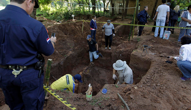 . Members of the police assist in excavating human remains discovered in the grounds of a police barracks in Asuncion March 21, 2013. According to the researchers, 15 more skeleton remains, likely to be victims of the 1954 to 1989 dictatorship under Alfredo Stroessner, were found in the last two days. REUTERS/Jorge Adorno