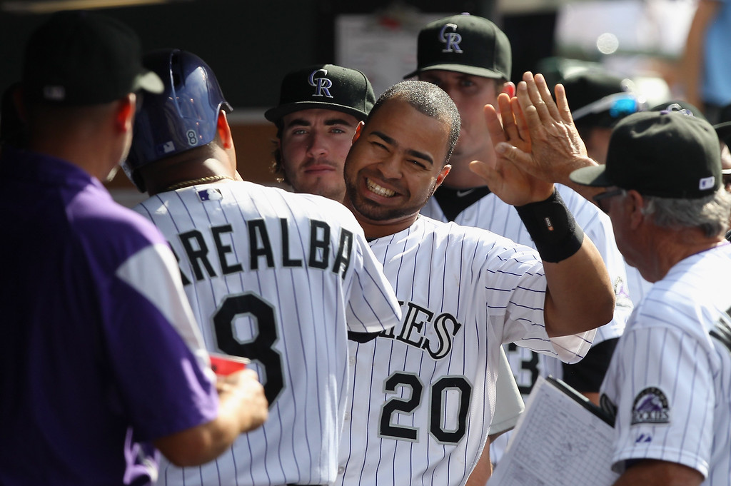 . Wilin Rosario #20 of the Colorado Rockies celebrates in the dugout after scoring the game winning run on a double by Nolan Arenado #28 of the Colorado Rockies off of Bryan Morris #29 of the Pittsburgh Pirates in the seventh inning at Coors Field on August 11, 2013 in Denver, Colorado. The Rockies defeated the Pirates 3-2.  (Photo by Doug Pensinger/Getty Images)