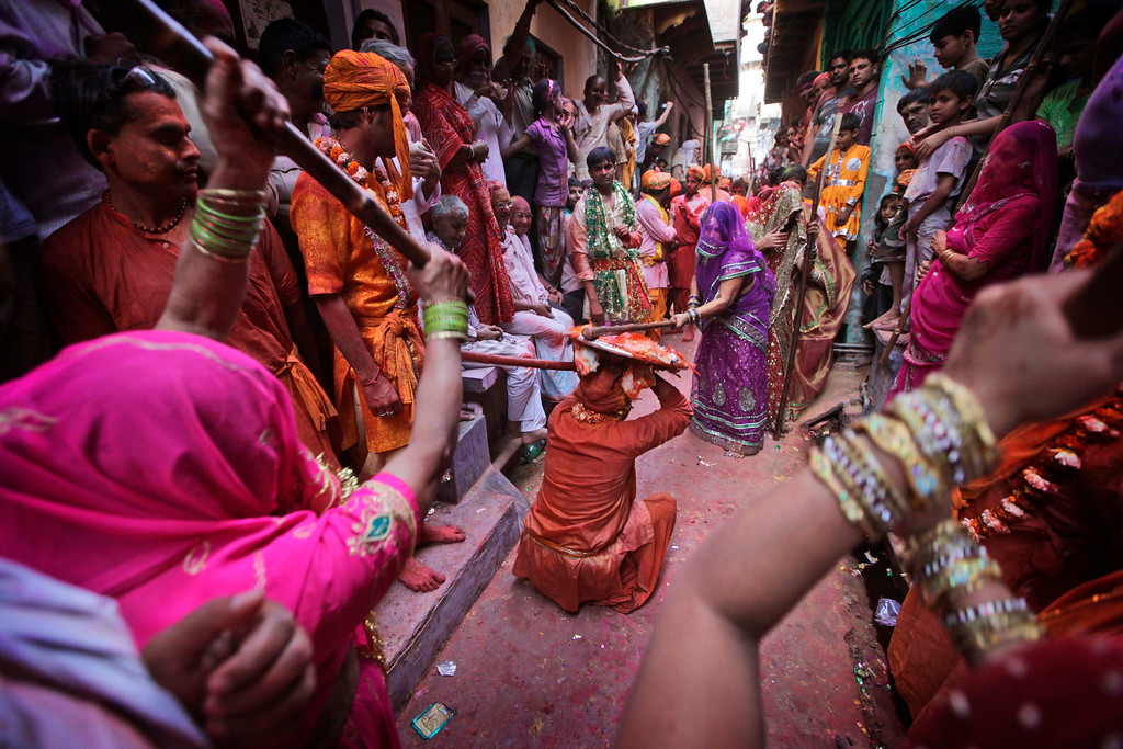 . Indian women from Barsana village hit villagers from Nandgaon with a wooden stick during the Lathmar Holy festival the legendary hometown of Radha, consort of Hindu God Krishna, in Barsana, 115 kilometers (71 miles) from New Delhi, India, Thursday, March 21, 2013. During Lathmar Holi the women of Barsana beat the men from Nandgaon, the hometown of Krishna, with wooden sticks in response to their teasing as they depart the town. (AP Photo/Manish Swarup)