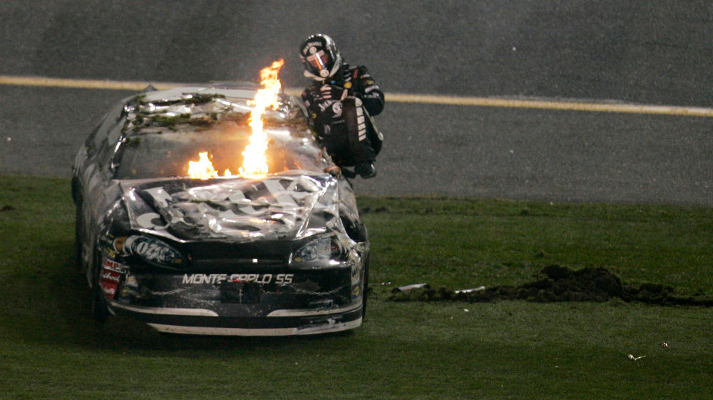 Description of . Clint Bowyer climbs from his car as flames rise from beneath the hood following the NASCAR Daytona 500 auto race at Daytona International Speedway in Daytona Beach, Fla., Sunday, Feb. 18, 2007. (AP Photo/J. Pat Carter)