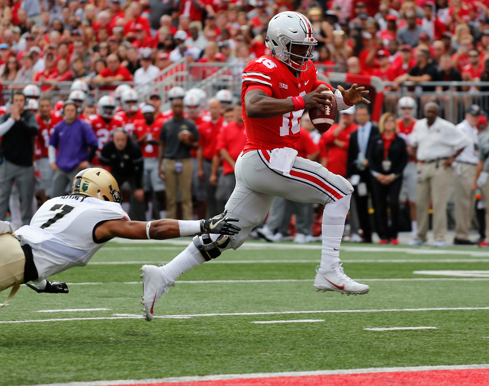 . Ohio State quarterback J.T. Barrett, right, scores a touchdown past Army defensive back Jaylon McClinton during the first half of an NCAA college football game Saturday, Sept. 16, 2017, in Columbus, Ohio. (AP Photo/Jay LaPrete)