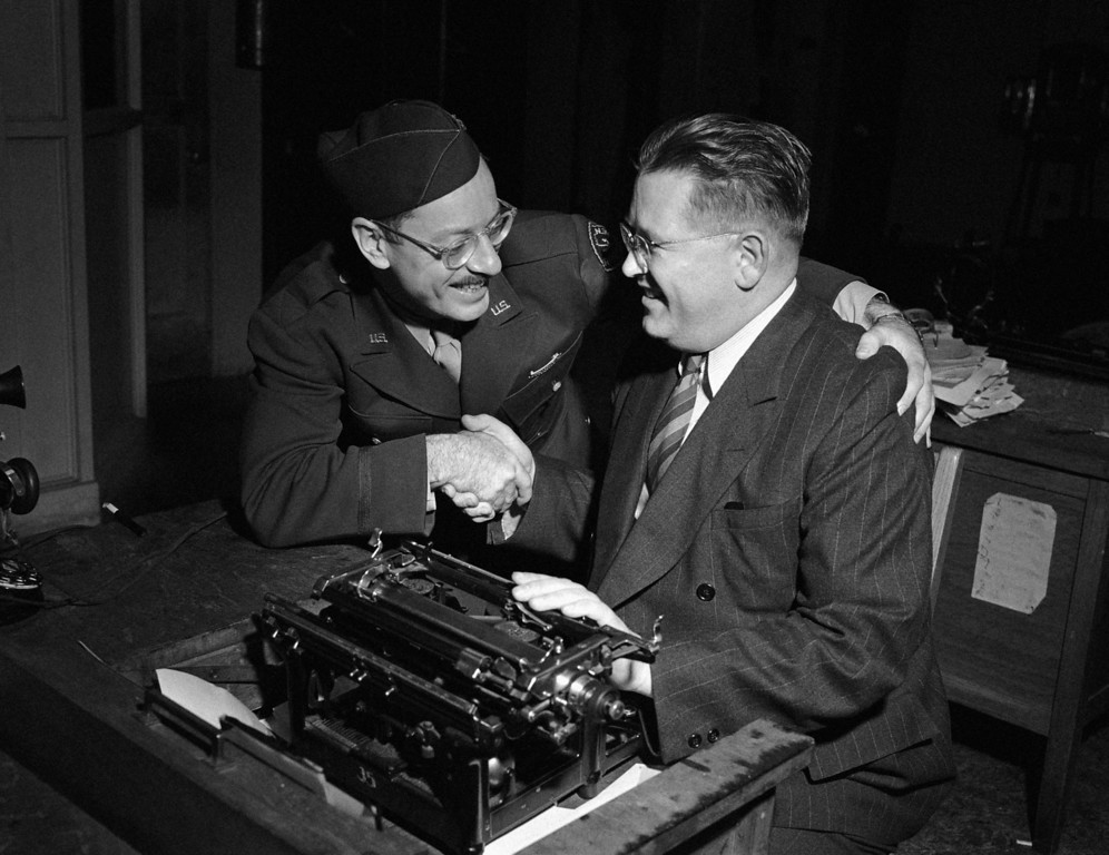 . Associated Press photographer Joe Rosenthal, left, and Jack S. McDowell of the San Francisco Call-Bulletin, both of whom won Pulitzer Prizes, congratulate each other in San Francisco, May 7, 1945.  (AP Photo/Ernest K. Bennett)