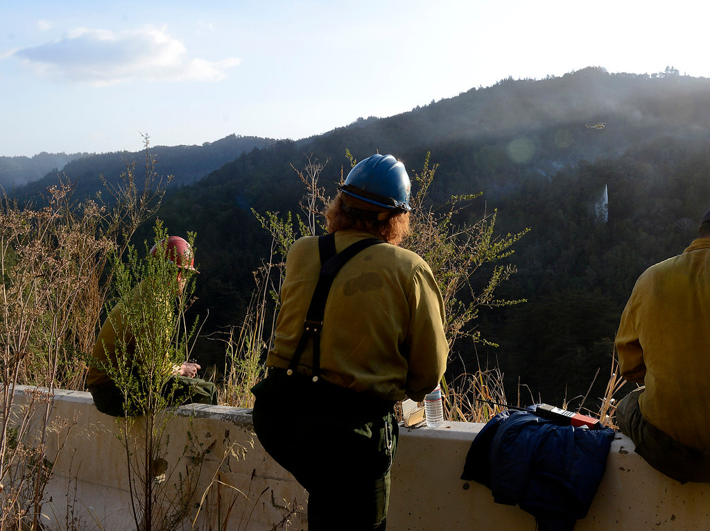 . Fire crew members watch as a helicopter makes a water drop on Pfeiffer Ridge above Fernwood in Big Sur, Calif. on Thursday December 19, 2013. (Photo David Royal/ Monterey County Herald)