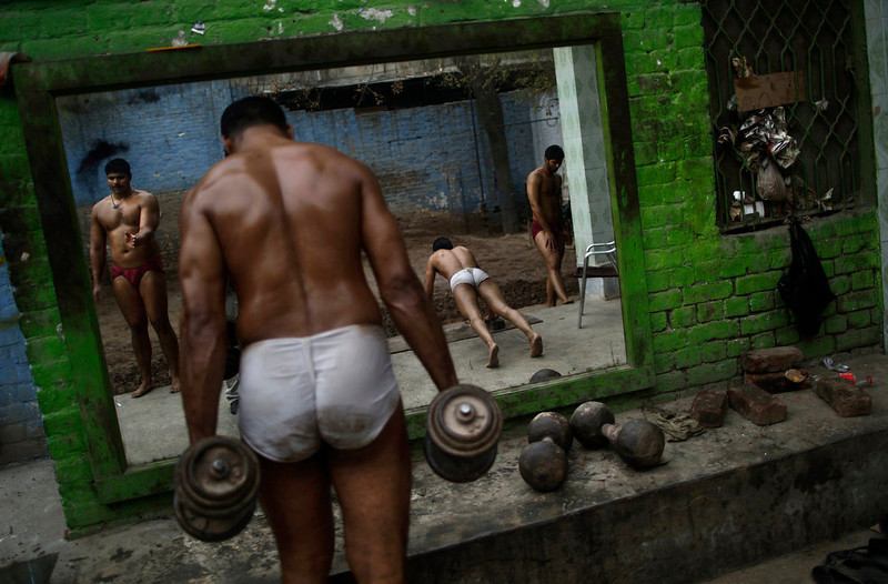 . Pakistani Kushti wrestlers warm up before attending their daily training session, at a wrestling club in Lahore, Pakistan, Tuesday, Feb. 26, 2013. Kushti, an Indo-Pakistani form of wrestling, is several thousand years old and is a national sport in Pakistan. (AP Photo/Muhammed Muheisen)