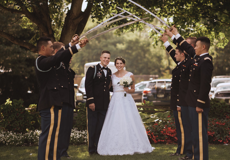 The bride and groom pose under an arch of swords held by the groom's fellow Army officers.