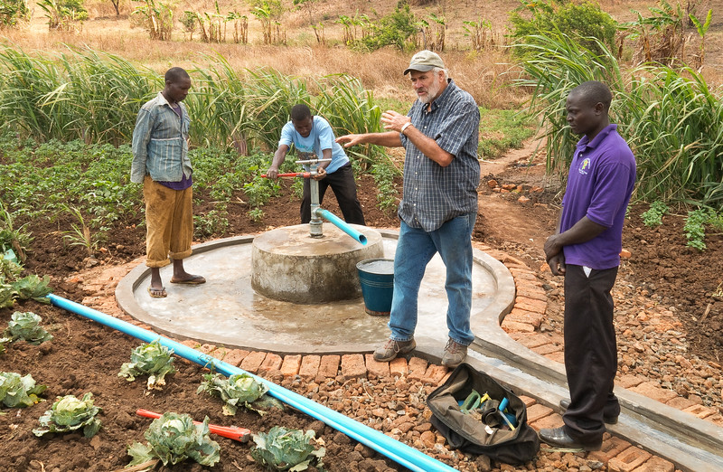 As a pump installation is completed, volunteers explain to the villagers how to use the well and properly care for it...