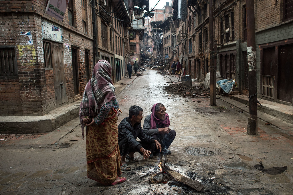 . Local residents warm themselves by a fire in the street in Bhaktapur on April 30, 2015 in Kathmandu, Nepal. A major 7.8 earthquake hit Kathmandu mid-day on Saturday, and was followed by multiple aftershocks that triggered avalanches on Mt. Everest that buried mountain climbers in their base camps. Many houses, buildings and temples in the capital were destroyed during the earthquake, leaving over 5500 dead and many more trapped under the debris as emergency rescue workers attempt to clear debris and find survivors. Regular aftershocks have hampered recovery missions as locals, officials and aid workers attempt to recover bodies from the rubble.  (Photo by David Ramos/Getty Images)