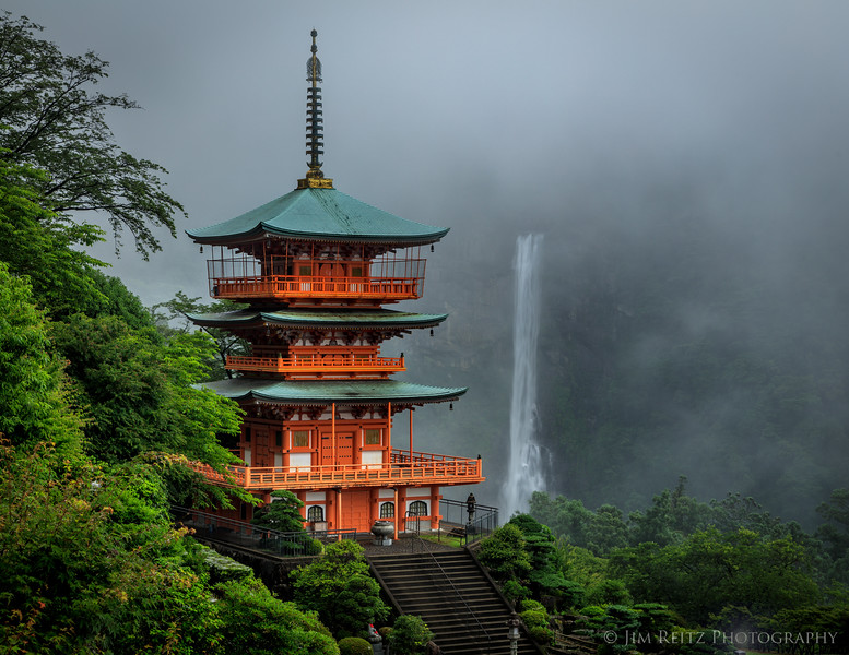 The pagoda of Sanjūdō temple, with Nachi Falls (Japan's tallest waterfall) briefly emerges from the fog. Near Nachikatsuura, Wakayama Prefecture, Japan.