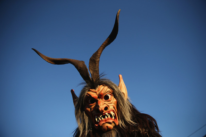 . A member of the Haiminger Krampusgruppe dressed as the Krampus creature arrives prior to the annual Krampus night in Tyrol on December 1, 2013 in Haiming, Austria. Krampus, in Tyrol also called Tuifl, is a demon-like creature represented by a fearsome, hand-carved wooden mask with animal horns, a suit made from sheep or goat skin and large cow bells attached to the waist that the wearer rings by running or shaking his hips up and down. Krampus has been a part of Central European, alpine folklore going back at least a millennium, and since the 17th-century Krampus traditionally accompanies St. Nicholas and angels on the evening of December 5 to visit households to reward children that have been good while reprimanding those who have not. However, in the last few decades Tyrol in particular has seen the founding of numerous village Krampus associations with up to 100 members each and who parade without St. Nicholas at Krampus events throughout November and early December.  (Photo by Sean Gallup/Getty Images)