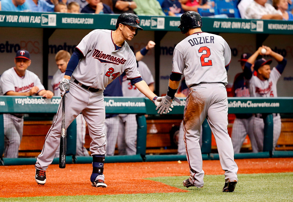 . Designated hitter Trevor Plouffe, left, congratulates teammate Brian Dozier, who scored on a Jamey Carroll single in the sixth inning. (Photo by J. Meric/Getty Images)