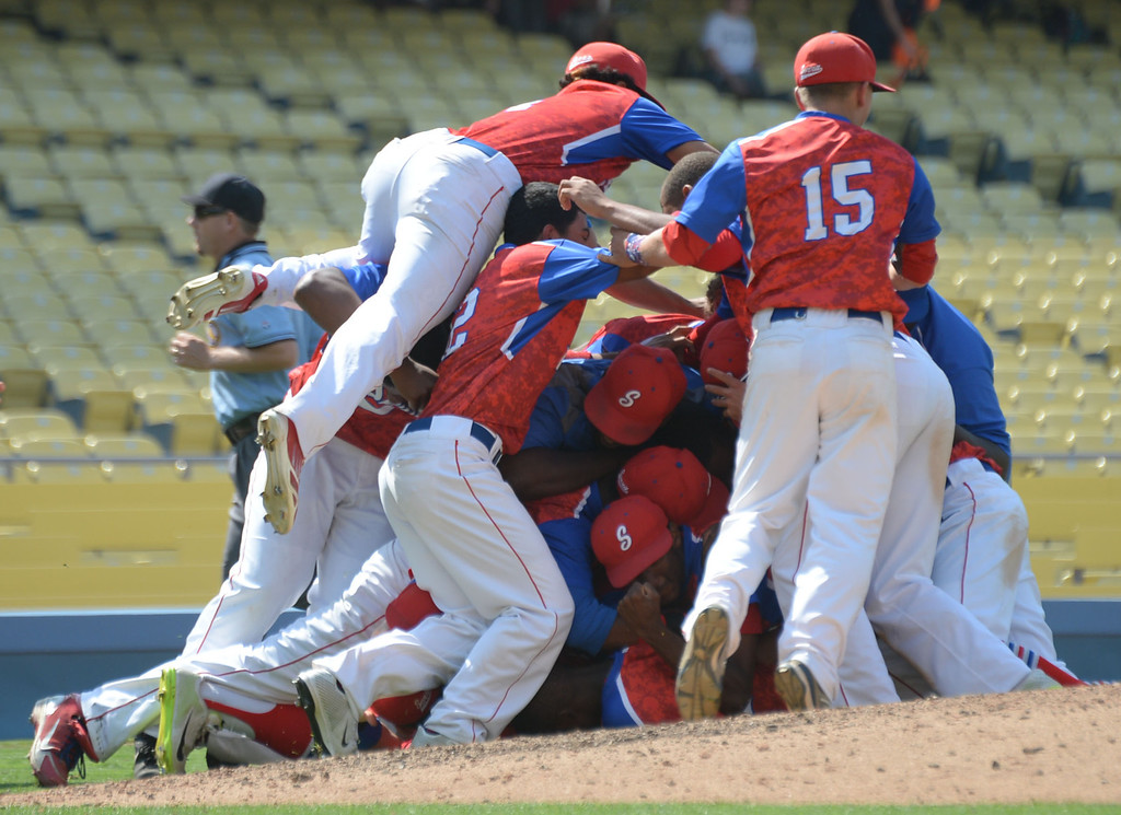 . Serra begins the dog pile as they celebrate their win against Mira Costa in the CIF-SS Division III championship baseball game Friday at Dodger Stadium. Serra won the title, 8-1. 20130531 Photo by Steve McCrank / Staff Photographer