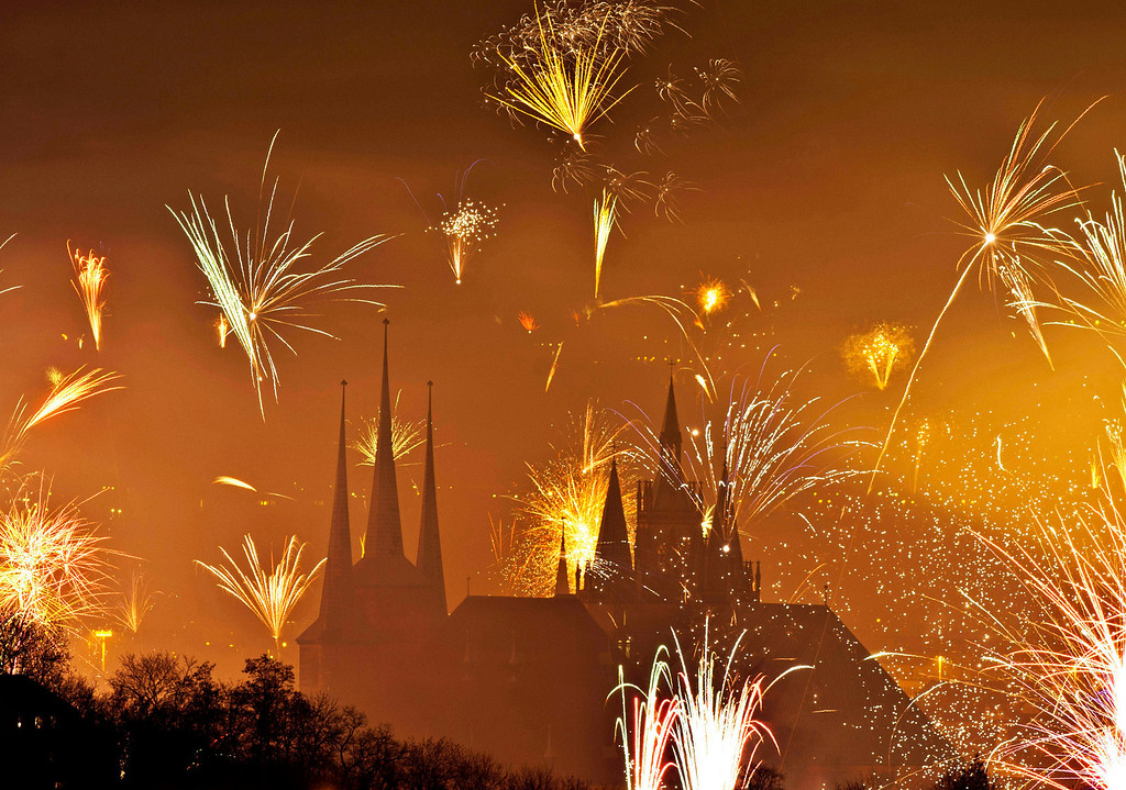 . Fireworks light the sky above the Mariendom (Cathedral of Mary), right, and the St. Severi\'s Church, left, shortly after midnight during New Year\'s Eve celebrations in Erfurt, central Germany, Wednesday, Jan 1, 2014. (AP Photo/Jens Meyer)