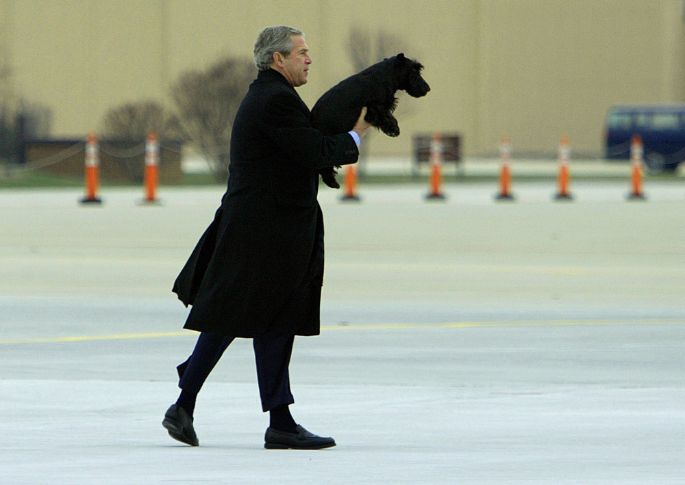 Description of . President Bush carries his dog Barney back to Air Force One after Barney wandered away at Andrews Air Force Base in Md., Sunday, Dec. 26, 2004. The Bush's will spend the New Year's holiday at their Crawford, Texas ranch.  (AP Photo/Susan Walsh)