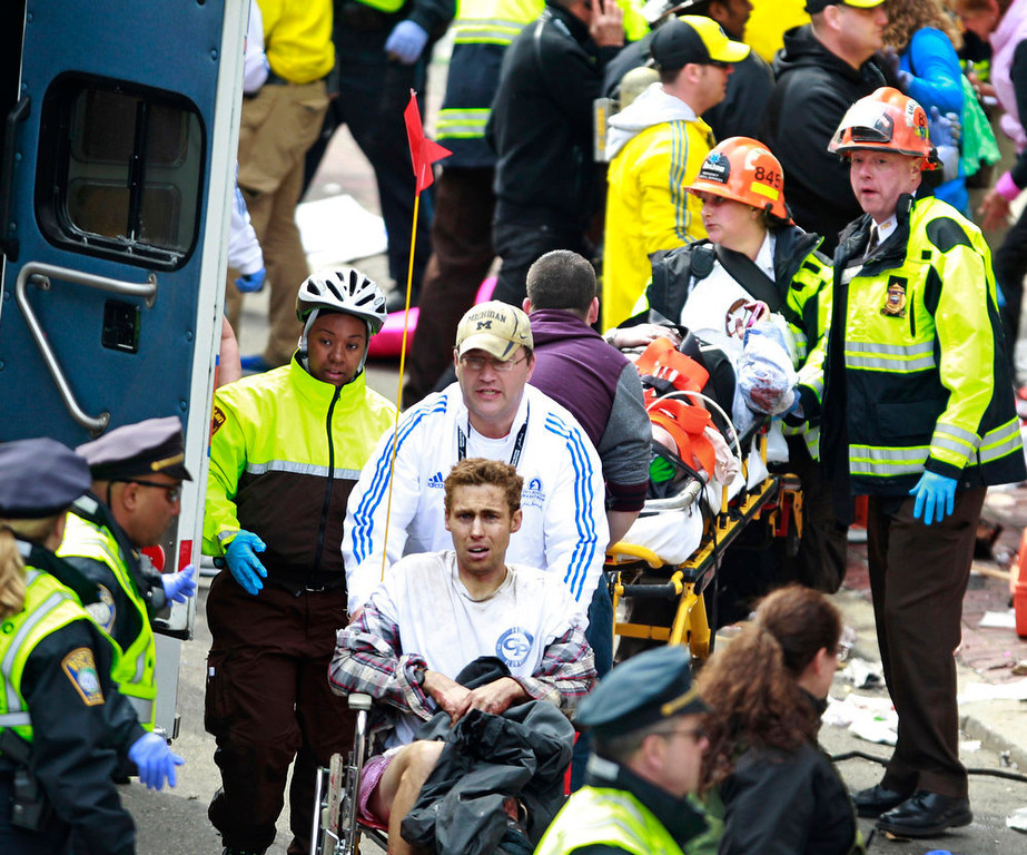 . Medical workers aid injured people at the finish line of the 2013 Boston Marathon following an explosion in Boston, Monday, April 15, 2013. Two explosions near the finish of the Boston Marathon on Monday, killing at least  two people, injuring over 20 others. (AP Photo/Charles Krupa)