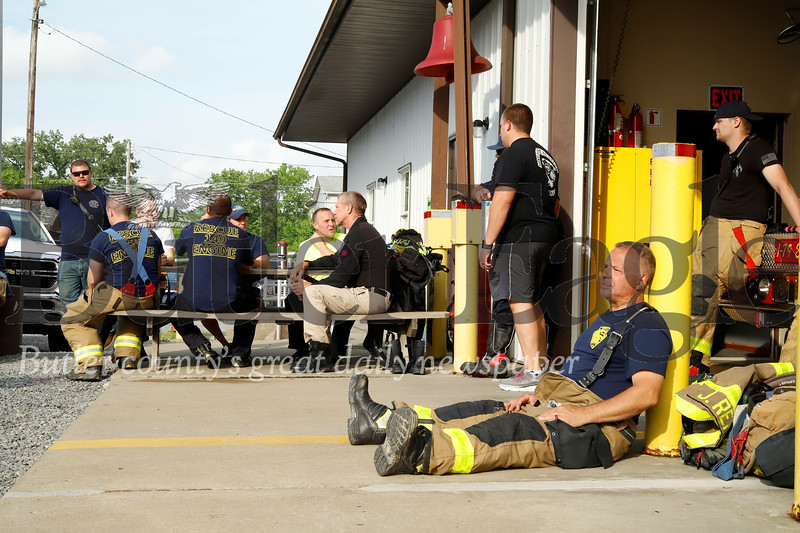 Eric DiBussi (right) of Shaler and members of the Harmony  and Etna Fire Departments take a break from a busy 24-hours of flood response efforts. DiBussi and other members of the Etna Fire Department came up Wednesday to assist in the aftermath of Tuesday night's storms. Seb Foltz/Butler Eagle