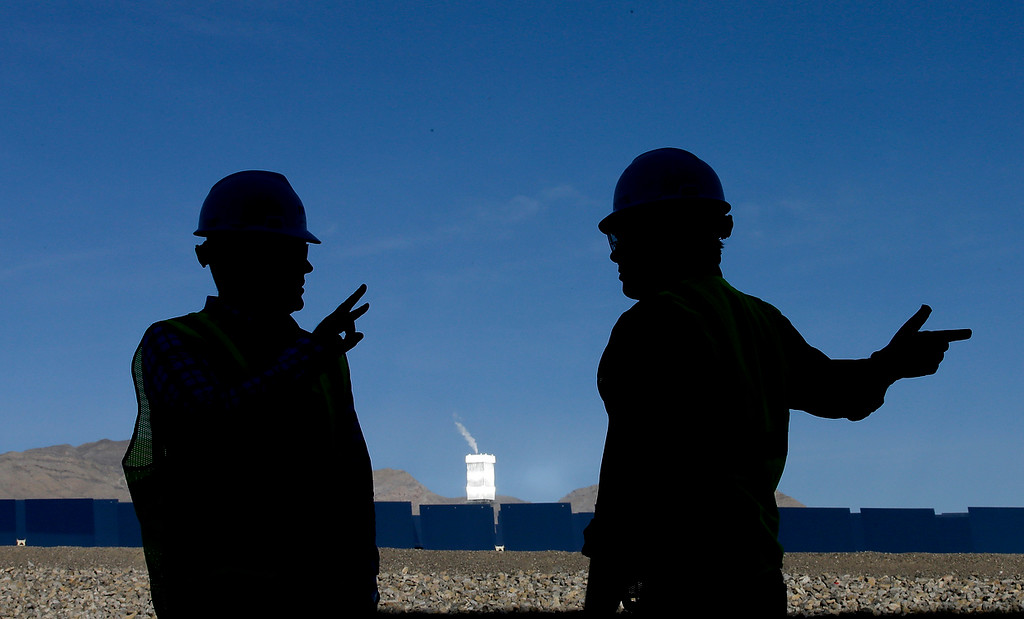 . Jeff Holland, right, talks with Noel Hanson  near a boilers that sit on 459-foot towers Tuesday, Feb. 11, 2014 in Primm, Nev. The Ivanpah Solar Electric Generating System, sprawling across roughly 5 square miles of federal land near the California-Nevada border. (AP Photo/Chris Carlson)