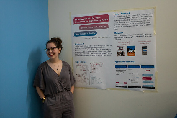 Eleanor Young, a second-year computer science AOC, stands by her poster describing her work to create a phone app to analyze digital content shared between users to flag potentially abusive behavior.