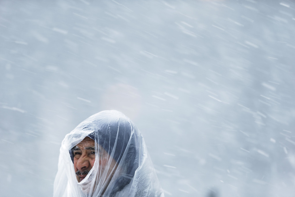 . A man peers through a hole in a plastic bag during a winter snowstorm Tuesday, Jan. 21, 2014, in Philadelphia. A storm is sweeping across the Mid-Atlantic and New England.  (AP Photo/Matt Rourke)