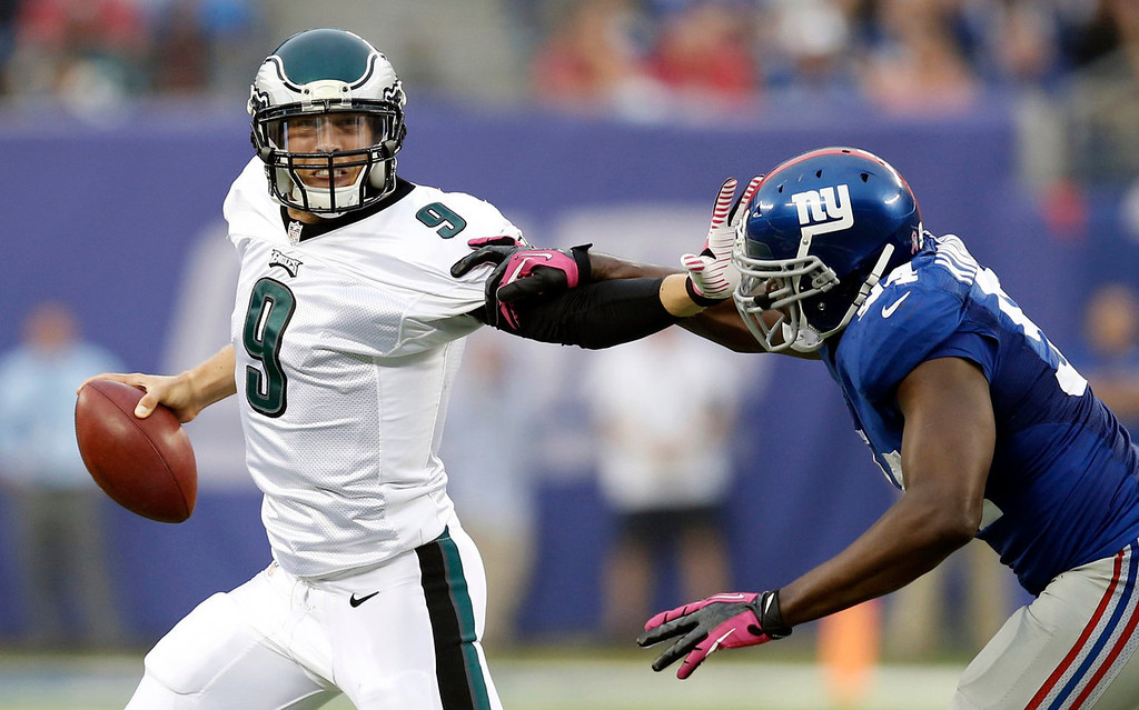 . Philadelphia Eagles\' Nick Foles (9) stiff-arms New York Giants\' Mathias Kiwanuka (94) during the second half of an NFL football game on Sunday, Oct. 6, 2013, in East Rutherford, N.J. (AP Photo/Kathy Willens)
