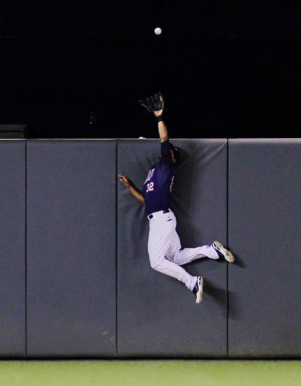 . Minnesota Twins center fielder Aaron Hicks  makes a leaping catch against Chicago White Sox\'s Adam Dunn\'s fly to center during the sixth inning of a baseball game, Monday, May 13, 2013, in Minneapolis. (AP Photo/Genevieve Ross)