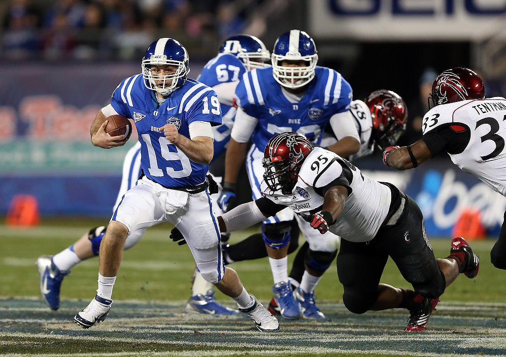 Description of . John Williams #95 of the Cincinnati Bearcats tries to stop Sean Renfree #19 of the Duke Blue Devils as he runs with the ball during their game at Bank of America Stadium on December 27, 2012 in Charlotte, North Carolina.  (Photo by Streeter Lecka/Getty Images)