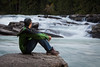 Man sitting by Rearguard Falls, Rearguard Falls Provincial Park, British Columbia, Canada.