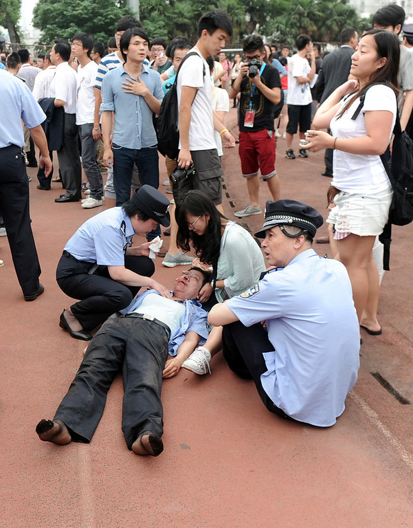 . An injured police officer receives assistance after being caught in a crush of people as David Beckham arrived at Tongji University on June 20, 2013 in Shanghai, China. The stampede is reported to have left five people injured and hospitalised. (Photo by Getty Images)