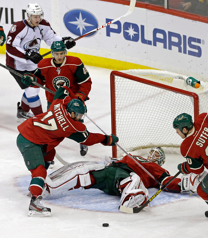. Minnesota Wild\'s Torrey Mitchell, left, and Ryan Suter, right, come to the aid of goalie Niklas Backstrom, of Finland, after he fell while protecting the net, as Colorado Avalanche\'s Gabriel Landeskog of Sweden, top left, skates in during the first period of an NHL hockey game Thursday, March 14, 2013, in St. Paul, Minn. (AP Photo/Jim Mone)
