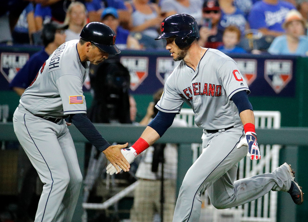 . Cleveland Indians\' Yan Gomes, right, celebrates with third base coach Mike Sarbaugh after hitting a grand slam during the sixth inning of the team\'s baseball game against the Kansas City Royals on Tuesday, July 3, 2018, in Kansas City, Mo. (AP Photo/Charlie Riedel)