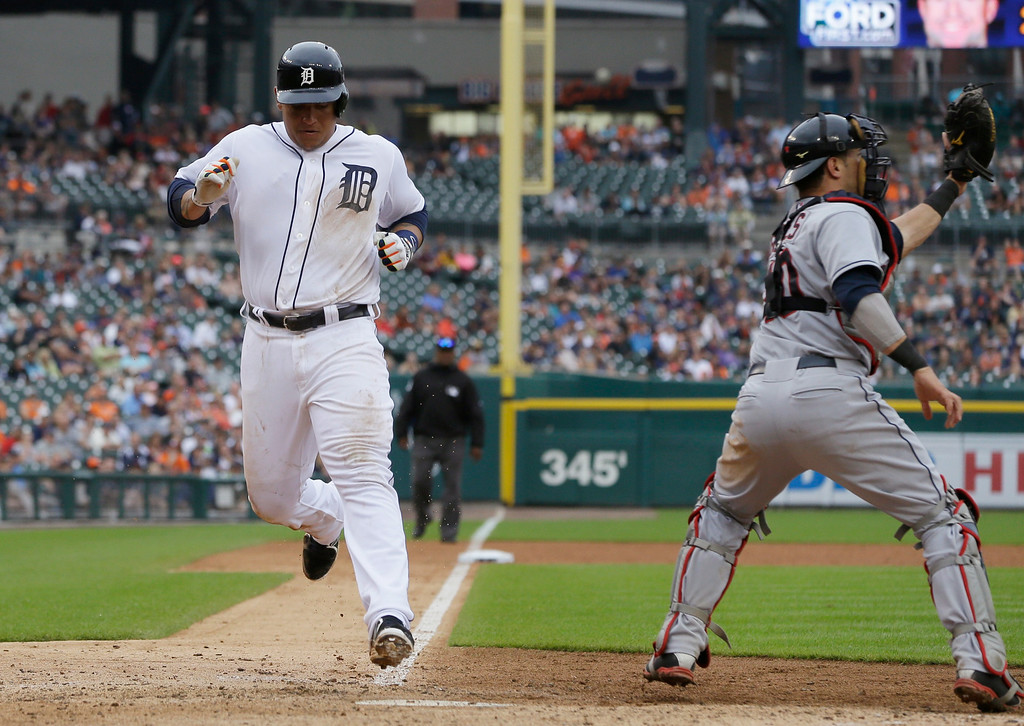. Detroit Tigers\' Miguel Cabrera scores ahead of the throw to Cleveland Indians catcher Yan Gomes during the ninth inning in the first baseball game of a doubleheader, Saturday, July 19, 2014 in Detroit. (AP Photo/Carlos Osorio)
