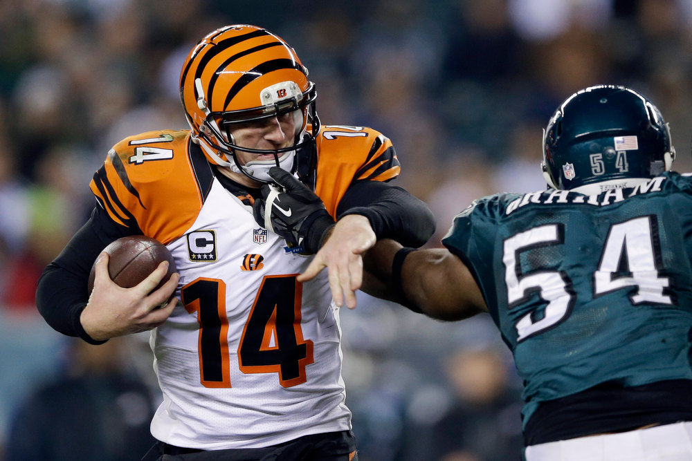 . Cincinnati Bengals\' Andy Dalton, left, tries to break free from Philadelphia Eagles\' Brandon Graham in the second half of an NFL football game, Thursday, Dec. 13, 2012, in Philadelphia. (AP Photo/Matt Rourke)