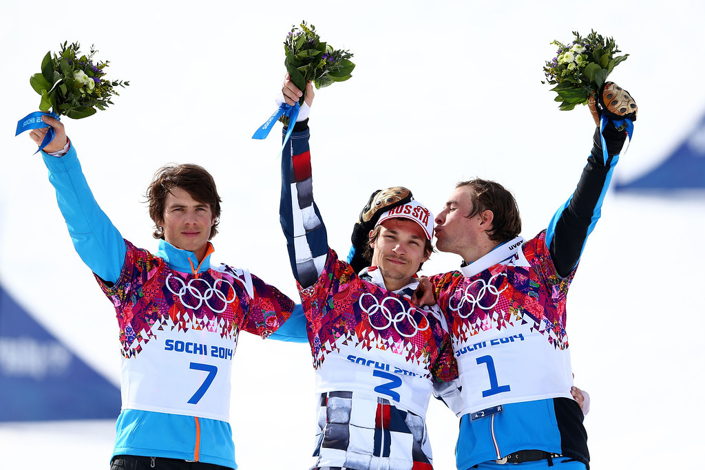 . SOCHI, RUSSIA - FEBRUARY 22:  Gold medalist Vic Wild (C) of Russia celebrates with silver medalist Zan Kosir (L) of Slovenia and bronze medalist Benjamin Karl of Austria during the flower ceremony in the Snowboard Men\'s Parallel Slalom Big Final on day 15 of the 2014 Winter Olympics at Rosa Khutor Extreme Park on February 22, 2014 in Sochi, Russia.  (Photo by Cameron Spencer/Getty Images)